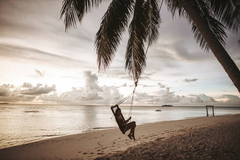 Woman on a swing at the sea at sunset, Maguhdhuvaa Island, Gaafu Dhaalu Atoll, Maldives - DAWF01231