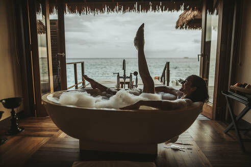 Woman relaxing in bathtub with view to the sea, Maguhdhuvaa Island, Gaafu Dhaalu Atoll, Maldives - DAWF01252