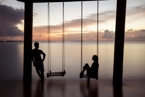 Couple on a swing at the sea at sunset, Maguhdhuvaa Island, Gaafu Dhaalu Atoll, Maldives - DAWF01258