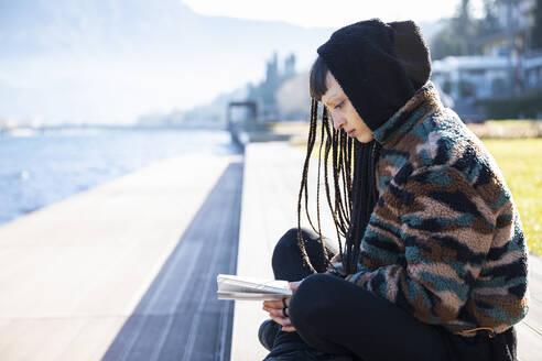 Young woman sitting on bench reading a book at Lake Como, Como, Italy - MCVF00201