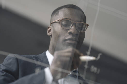 Portrait of young businessman drawing diagram on glass pane in office - KNSF07412