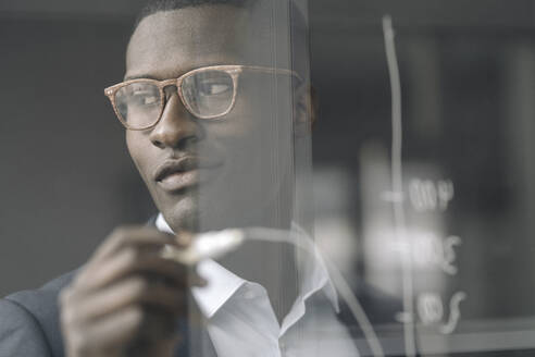 Portrait of content young businessman drawing diagram on glass pane - KNSF07415