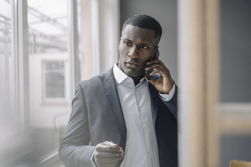 Portrait of young businessman on the  phone - KNSF07424