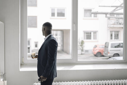 Businessman with paper cup and smartphone looking out of window - KNSF07430