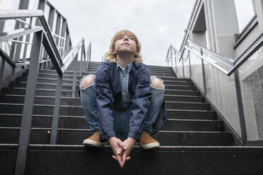 Portrait of blond boy crouching on stairs outdoors looking up - EYAF00924