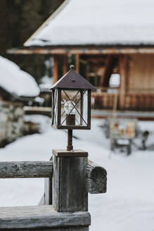 Italy, Bolzano, Alpe di Siusi, Lantern on wooden fence in front of cottage house in snow - LSF00090