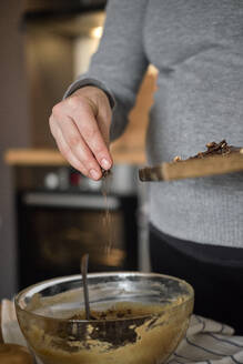Pregnant woman making healthy cake with tahini, walnuts and dark chocolate at home - BZF00515