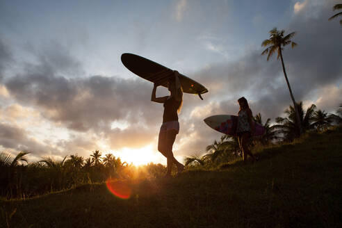 Two women carrying surfboards on a hill during sunset on Siargao Island, Philippines - FAF00084