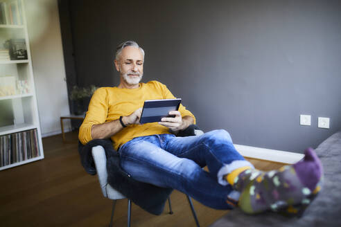 Relaxed mature man at home using tablet - FMKF06109