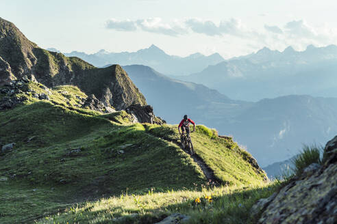 Mountainbiker on a way on a ridge, Grisons, Switzerland - HBIF00011