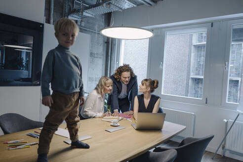 Boy standing on table in office with business team having a meeting - KNSF07473
