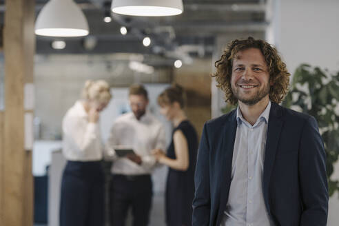 Portrait of confident businessman in office with colleagues in background - KNSF07479