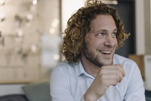 Portrait of happy businessman having a break in office - KNSF07488