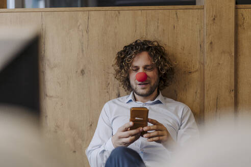 Businessman with red clown nose using cell phone in office - KNSF07503