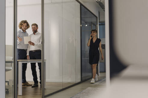 Two businessmen using tablet in office with businesswoman on the phone passing by - KNSF07506