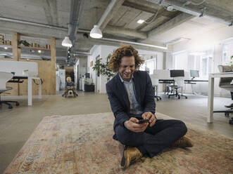 Businessman sitting on carpet in office using cell phone with son in background - KNSF07518