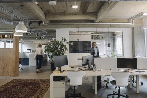 Businessman and businesswoman in modern office - KNSF07530