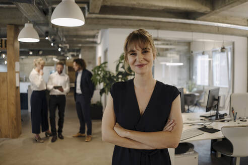 Portrait of confident businesswoman in office with colleagues in background - KNSF07548
