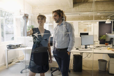 Businessman and businesswoman working on a project in office - KNSF07551