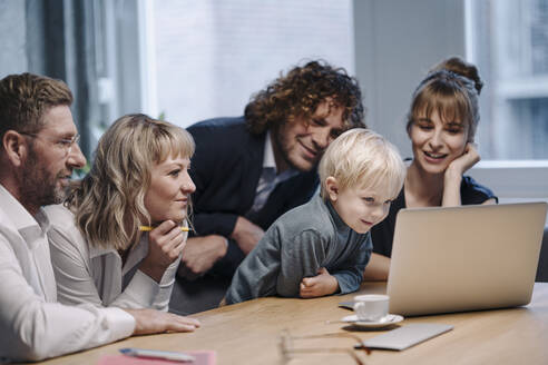 Business team with boy looking at laptop in office - KNSF07572