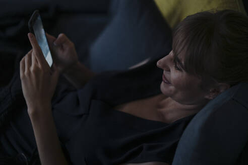 Smiling woman using cell phone on couch - KNSF07590