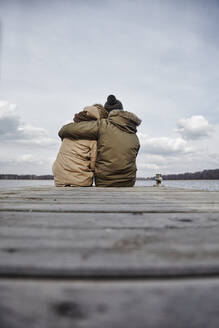 Back view of young couple in love sitting on a jetty looking at lake in winter - ANHF00156