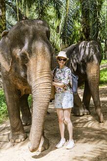 Portrait of smiling woman with elephants in sanctuary, Krabi, Thailand - CHPF00600