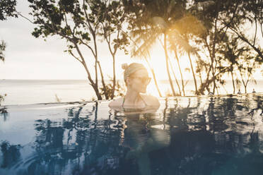 Woman in infinity pool at sunset, Nai Thon Beach, Phuket, Thailand - CHPF00618