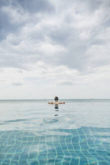 Rear view of woman in infinity pool, Koh Lanta, Thailand - CHPF00633