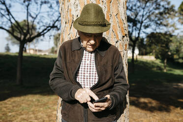 Old man using smartphone, leaning on tree trunk - JRFF04105