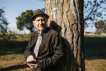 Old man using smartphone, leaning on tree trunk - JRFF04108