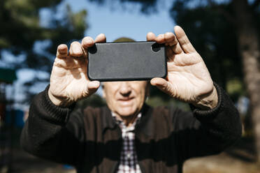 Old man taking pictutes with his smartphone - JRFF04111