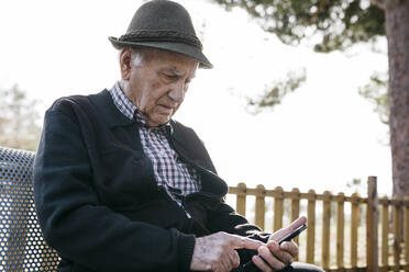 Old man with, sitting on bench, using smartphone - JRFF04114