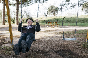 Old man swinging on playground in park - JRFF04117