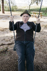 Old man swinging on playground in park - JRFF04120