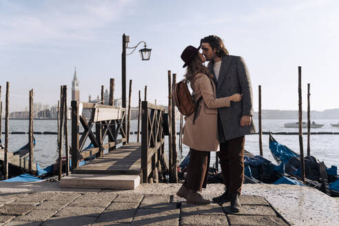 Young couple kissing at the waterfront in Venice, Italy - MAUF03263