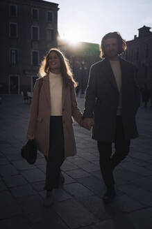 Young couple visiting the city of Venice, Italy, at sunset - MAUF03281