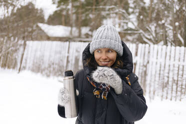 Portrait of smiling woman using thermo flask in winter - KNTF04197