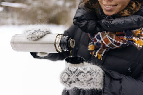 Crop view of woman pouring tea into thermo mug in winter - KNTF04200