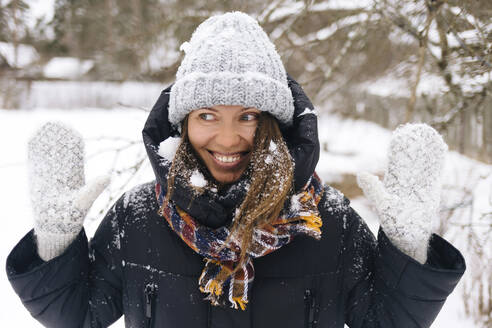 Portrait of woman enjoying snowfall - KNTF04209