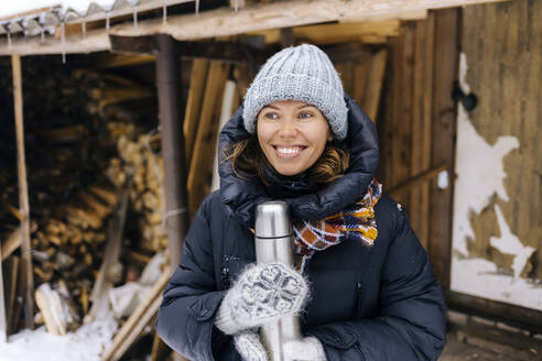 Portrait of happy woman with thermo flask in winter - KNTF04212