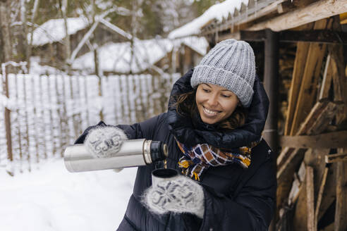 Portrait of happy woman using thermo flask in winter - KNTF04215