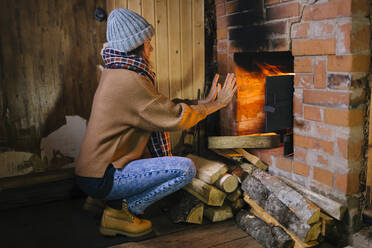 Woman crouching in front of fireplace warming her hands - KNTF04218
