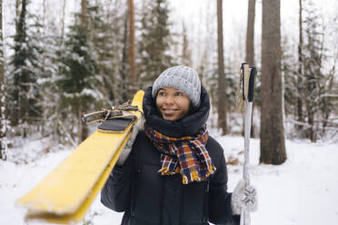 Portrait of smiling woman with skis in winter forest - KNTF04220