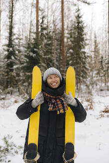 Portrait of smiling woman with skis in winter forest - KNTF04223