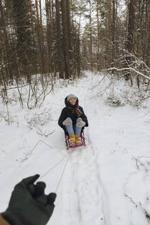 Man's hand pulling woman sitting on a sledge - KNTF04232