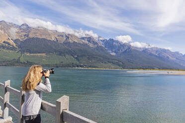New Zealand, Oceania, South Island, Otago, Lake Wakatipu, New Zealand Alps, Glenorchy, Woman photographing landscape from pier - FOF11758