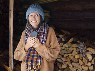 Young woman near a woodpile holding smartphone - KNTF04237