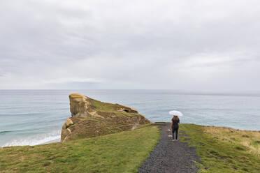 New Zealand, Oceania, South Island, Otago, Dunedin, Rear view of woman with umbrella on footpath nearTunnel Beach - FOF11798