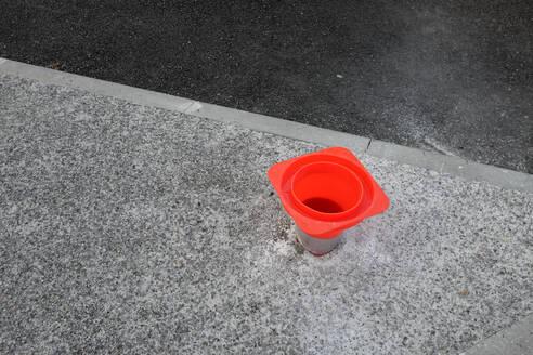 France, Brittany, Audierne, Orange traffic cone upside down in asphalt hole - GISF00501